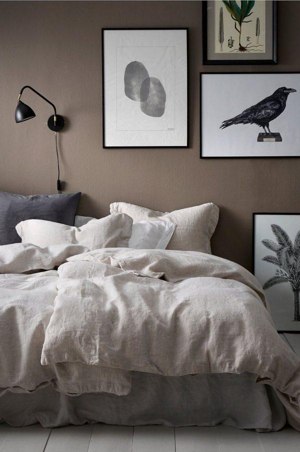 Soveværelse der emmer af hygge og romantik. Væggen er lys brun og gør rummet hyggeligt. På væggen hænger et miks plakater i rammer og sengen er lækkert med hørsengetøj i naturfarver.
