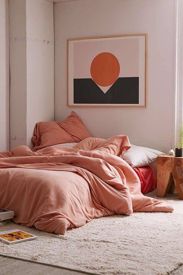 Boheme hippie soveværelse af den lækre type. Madras på gulvet ferskenfarvet sengetøj og en smukt grafisk værk på væggen i samme farver som sengetøjet.