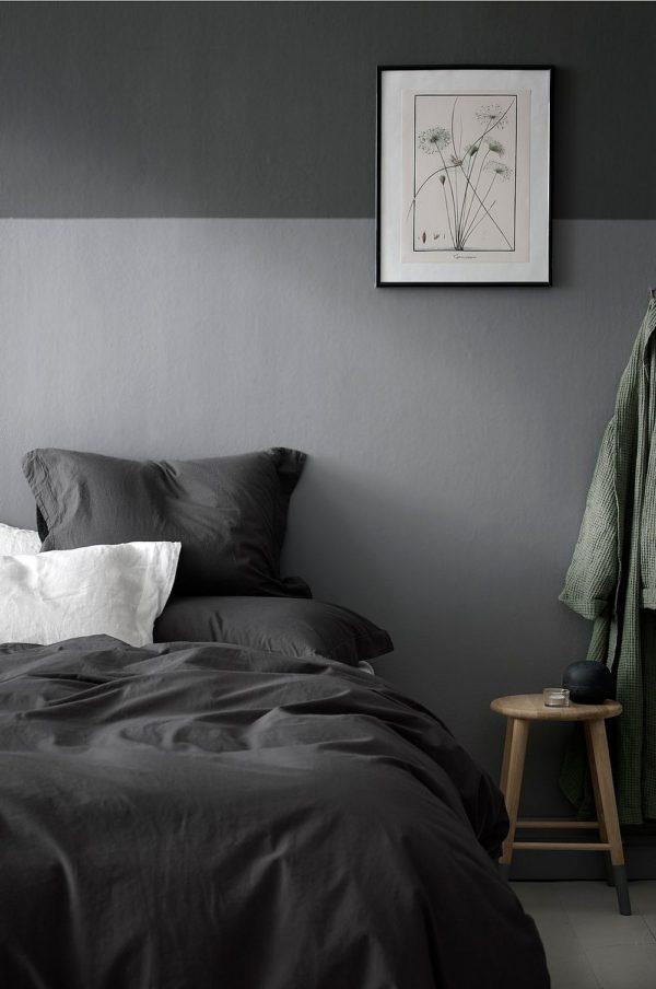 Soveværelsesindretning holdt i grå nuancer. Væggen er malet lysgrå på den nederste halvedel og mørekgrå på den øverste halvdel.