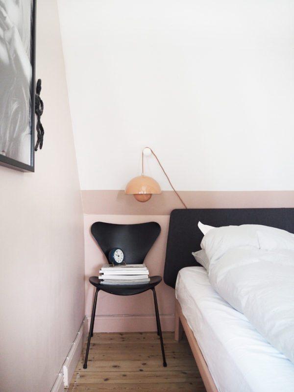 Et hjørne af et soveværelse som illustrerer at man sagtens kan bruge Arne Jacobsens 7'er stol som sengebord