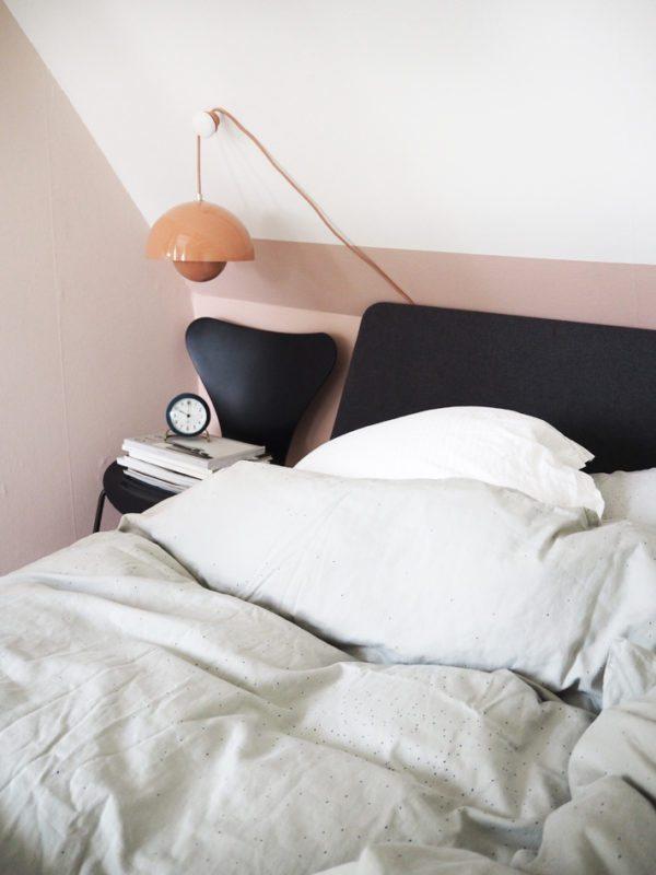 Soveværelse med skråvægge. Halvdelen af væggen er malet pudderfarvet. På væggen hænger en Laksefarvet Flowerpot lampe fra Panton. Senge fra Auping har polstret gråt hovedgærde.
