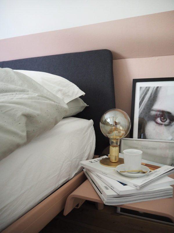 På billedet ses et hjørne fra et soveværelse med pudderfarvede vægge og en en Auping seng med mørkegråt hovegærde. Sengbord monteret på sengen, her står en lampe i messing