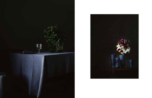 stemningsfuldt og mørkt billede hvor enden af et spisebord anes i mørket. over bordet ligger en mørk hørdug