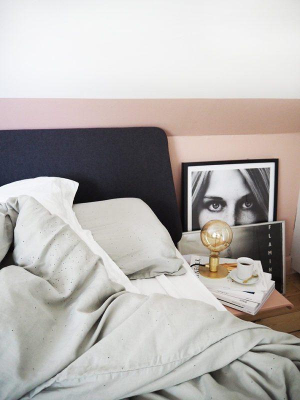 På billedet ses et hjørne fra et soveværelse med pudderfarvede vægge og en en Auping seng med mørkegråt hovegærde. På gulvet stor indrammede sort/hvid fotoplakater