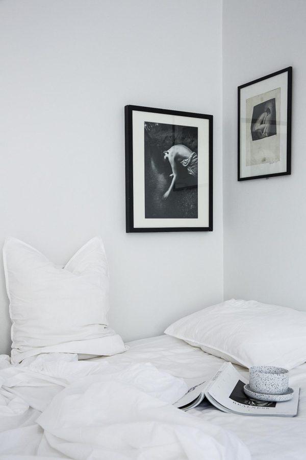 sovekrog holdt i hvid med flot fotokunst på væggen.