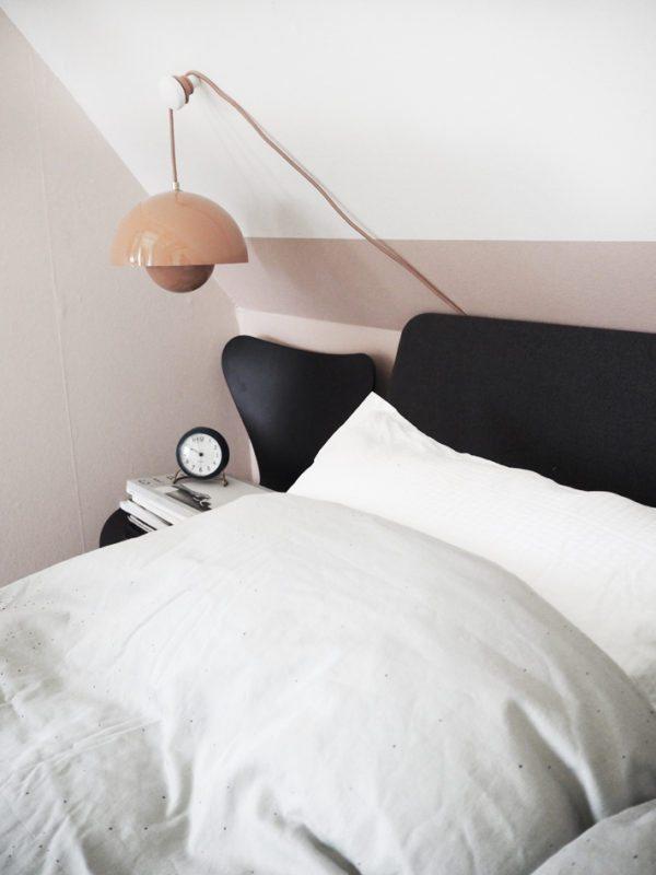 Soveværelse med rosa vægge, en Auping Essential seng med gråt hovegærde. PÅ væggen hænger en Flowerpot lampe i ferskenfarvet