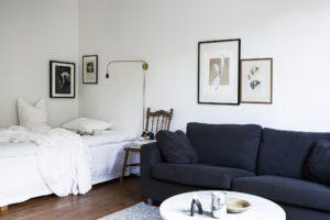 Stue og soveværelse i et. Hyggelig sovekrog holdt i hvidt. Mørkeblå sofa ot rundt sofabord.
