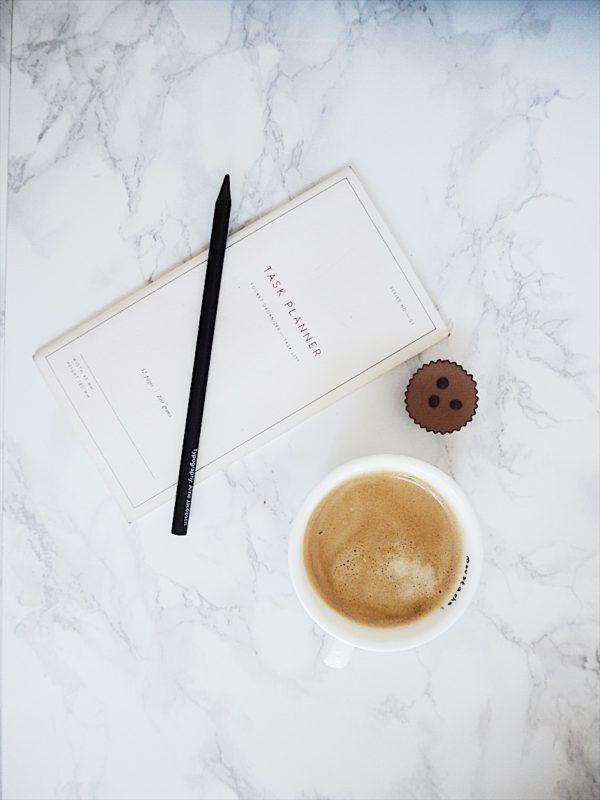 på billedet ses en kop kaffe, en notesbog og en chokolade