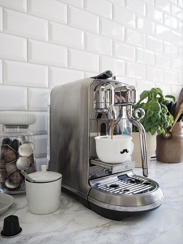 Hyggeligt café område i køkkenet med Nespresso maskine der brygger kaffe