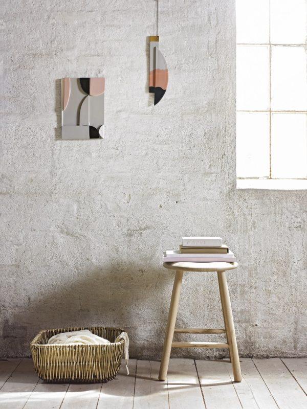 Kunst relieffer i ler med smukke farvet glasuer. Der hænger to på en rå væg.