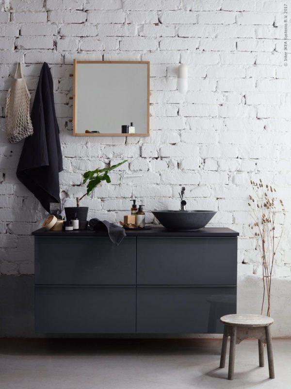 Badeværelse med sorte IKEA møbler monteret på rå og forfalden murstensvæg.