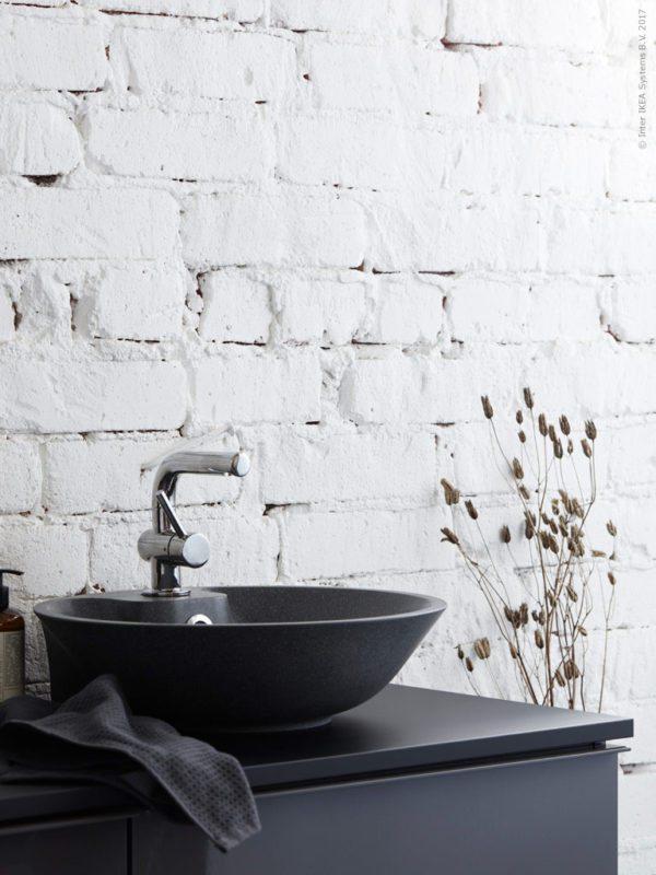 Nærbillede af en sort håndvask monteret på sort underskab fra IKEA.