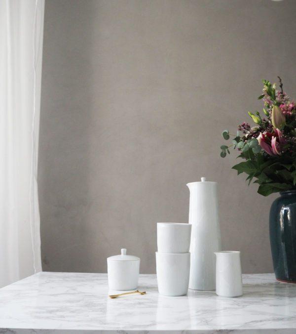 En opstilling på et bord med Thermodan termokande, kopper, flødekande og sukkerskål fra Lyngbyporcelæn. Serien står placret på et hvidt marmorbord. Ved siden af står en smuk tosabuket blomster i en grøn vase og vægge i baggrunden er smuk og stemningsfuld i rå lys grå betonmaling