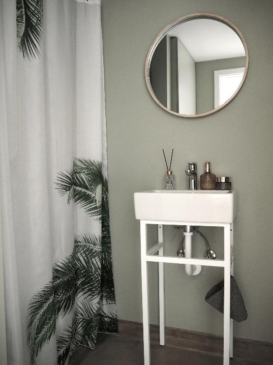 Flot vadeværelse med grønne vægge og palme bruseforhæng
