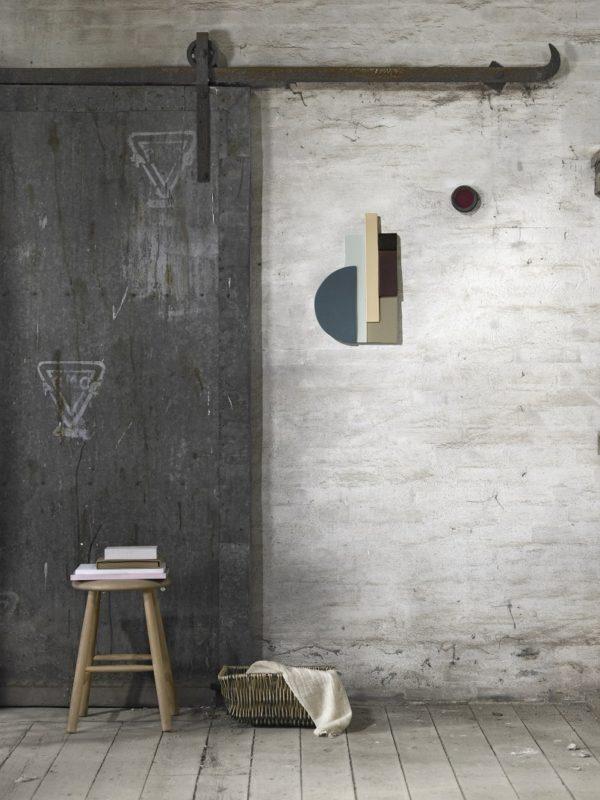 Kunst relief i ler med smukke farver og med blank glasuer. Relieffet hænger her på en rå væg