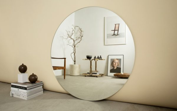 stort rundt spejl placeret på gulvet og afspejler et hjørne af et rum med fotokunst på væggen
