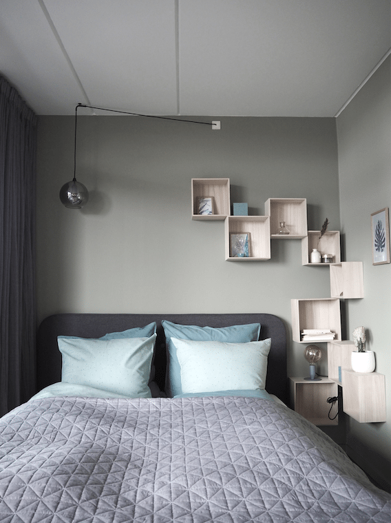 Smukt soverum med grå sengegavl og grønne vægge