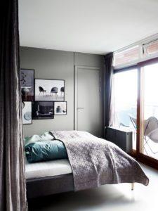 Sovevaerelse med grå vægge. Soveværelset er i åbent rum sammen med den øvrige lejlighed, så man har sat et gardin op som kan trække fra når man vil have privatliv