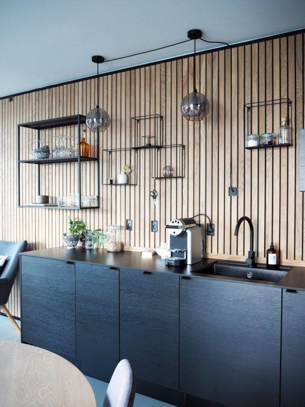 Flot køkken med træbeklædte vægge og sorte køkken elementer