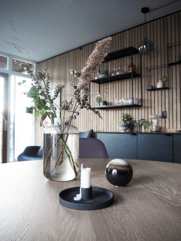 Et kig ind i et køkken alrum. Der er stillet skarp på et fint stilleben på spisebordet. En lille gruppe med en vase, et lys og en dekorationskugle i glas. I baggrunden ses en flot træbeklædt væg