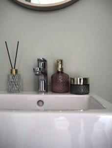 Med ganske få detaljer oser badeværelset af feminine detaljer som de fine glasbeholdere her.