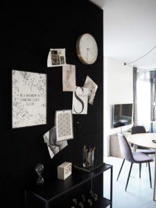 Et kig ind i en lejlighed, vi ser en sort væg med opslagstavle og et lille glimt af spisestuen