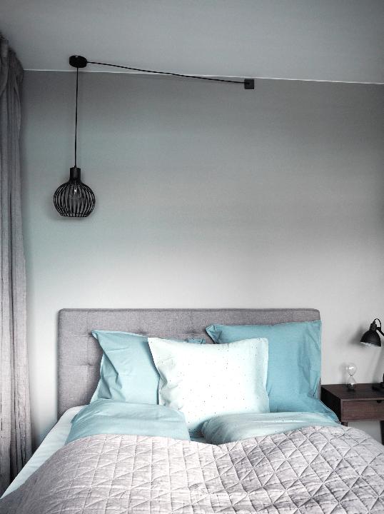 Hotelværelse med grå vægge og seng med polstret hovegærde