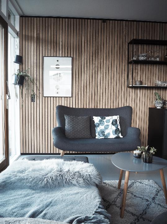 To personers sofa fra Jysk placeret i en stue med flotte træbeklædte vægge