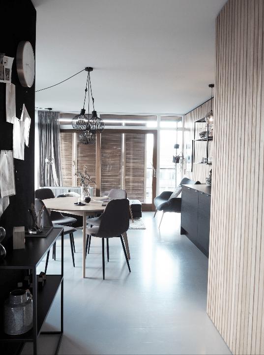 Hotel lejlighed med rundt spisebord og træbeklædte vægge