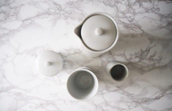 En opstilling på et bord fotograferet oppefra med Thermodan termokande, kopper, flødekande og sukkerskål fra Lyngbyporcelæn
