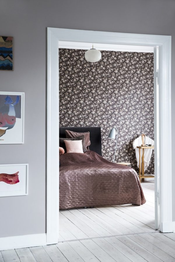 Et kig ind i et skønt soveværelse med brunblomstret tapet og seng med brunlig velour sengetæppe.