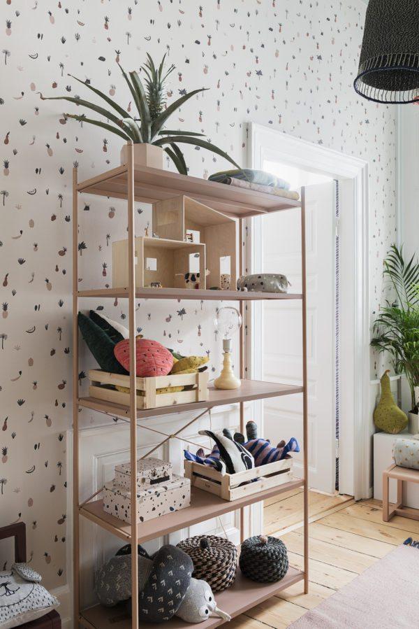 Et børneværelse med tapet fra Ferm Living på væggene. i rummet står en fin reol i rosa med masser af legetøj og bamser