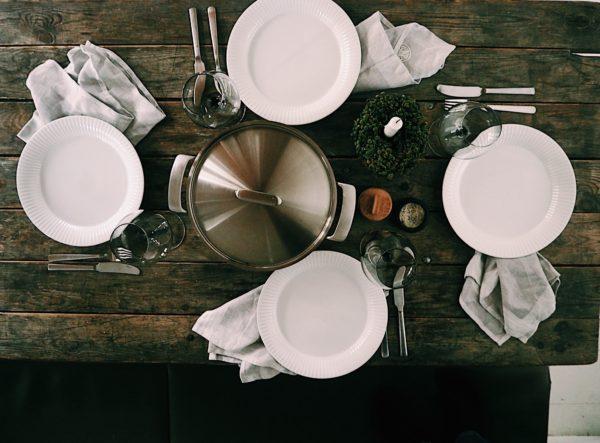 Dækket bord ses oppefra, med hvide tallerkner høje glas på rustikt plankebord