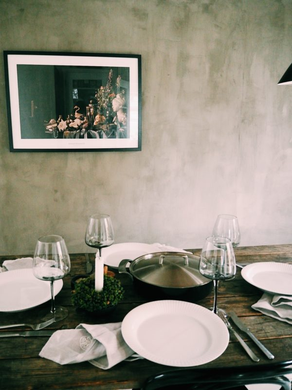 Dækket middagsbord med stegepanden direkte på bordet. i baggrunden ses en smuk grå rustik væg