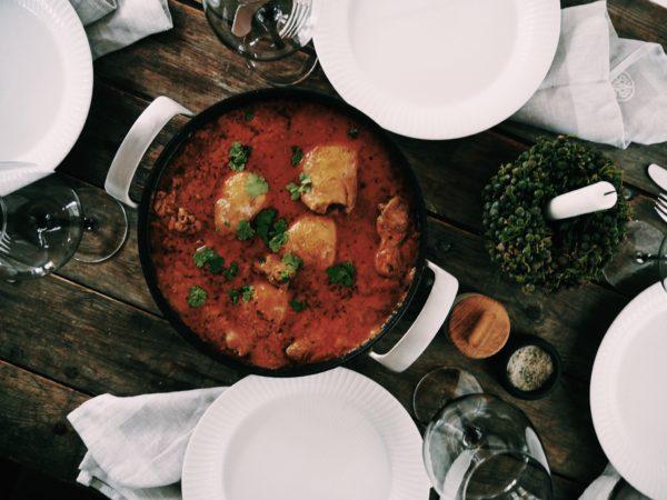 Middagsbord ses oppefra. Hvide tallerkner og stegefad med lække kyllingegryderet placeret på råt plankebord
