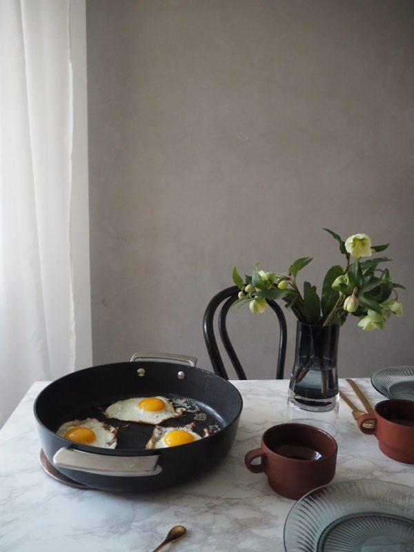 Morgenbord med spejlæg og kaffe placeret på flot marmor bord med franske cafestole omkring.
