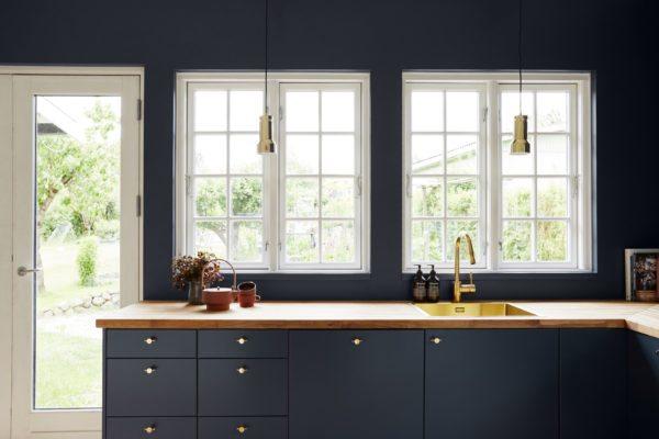 Smukt kuøkken med blå vægge og skabe, messing greb og armatur og fine messing pendler og køkkenbordet