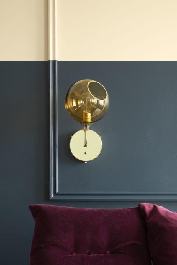 DIY: Soveværelse med væg malet i to farver, støvet blå forneden og cremehvid for oven. Bag sengen er monteret en liste i en firkant som danner en tom ramme. Listerne er malet samme farve som væggen. Elegant udtryk