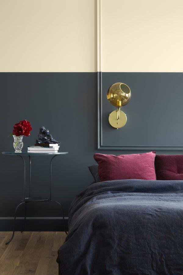 DIY: Soveværelse med væg malet i to farver, støvet blå forneden og cremehvid for oven. Bag sengen er monteret en liste i en firkant som danner en tom ramme. Listerne er malet samme farve som væggen.