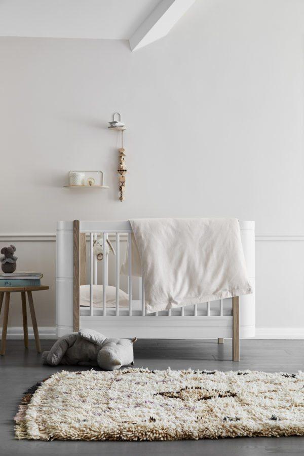 Babyværelse med høj tremmeseng og sart rosa vægge og sengetøj. Et dejligt fredfyldt rum
