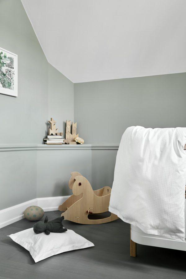 SKønt babyværelse med høj seng og støvede grønne skrå vægge. På gulvet står en skøn gyngehest i træ.