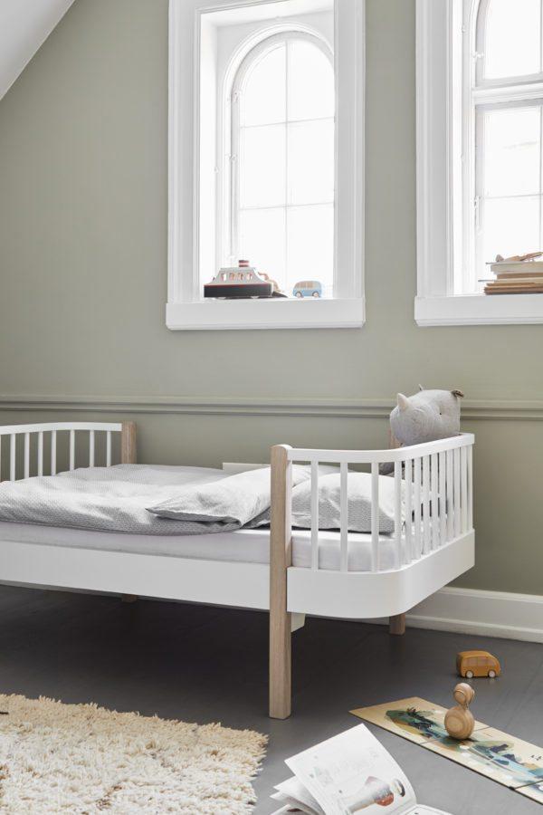 Smukt børnværelse med smuk skandinavisk seng i hvid og lys træ. Her er højt til loftet, smukke buede hvide vinduer og støvede grønne vægge