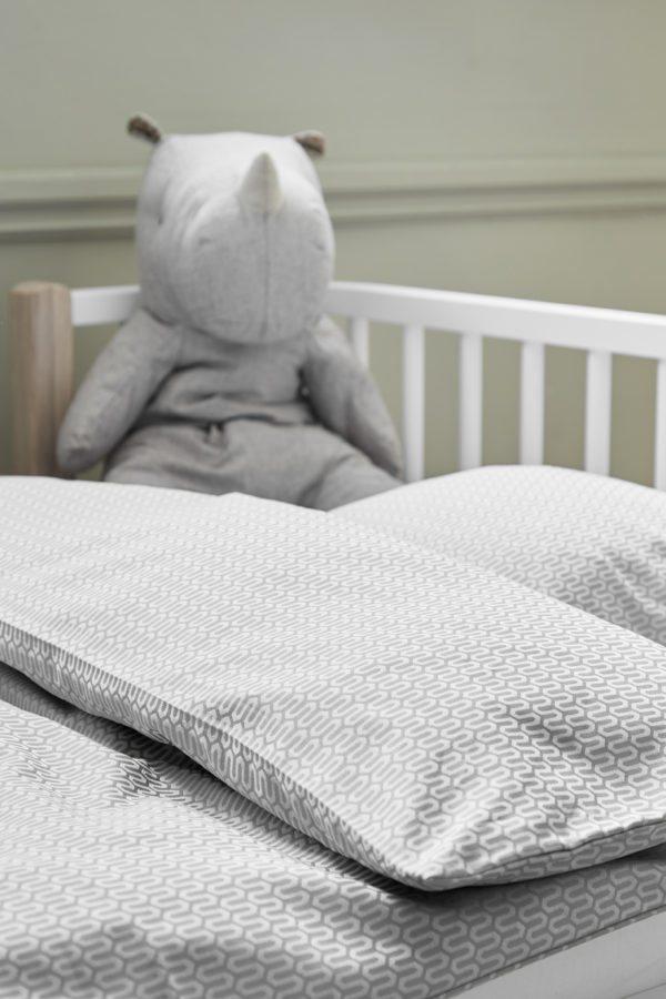 nærbillede af en seng med smukt sengetøj fra Georg jensen Damask og en sovebamse fra Maileg