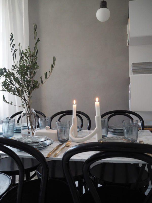 Bordedækning i stue med grå vægge. Bordet med marmorplade er dækket med blå glas og glastallerkner i Hammershøiserien fra Kähler Design. Levende lys og smukke olivengrene sætter en skøn stemning
