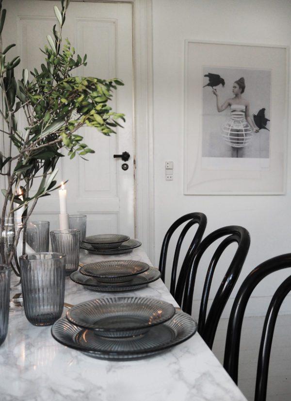 Bordet er dækket til fest med Kählers Hammershøi glas tallerkner i blå. Franske cafestole danner en stemningsfuld ramme og fine olivengrene pynter på bordet i stuen.