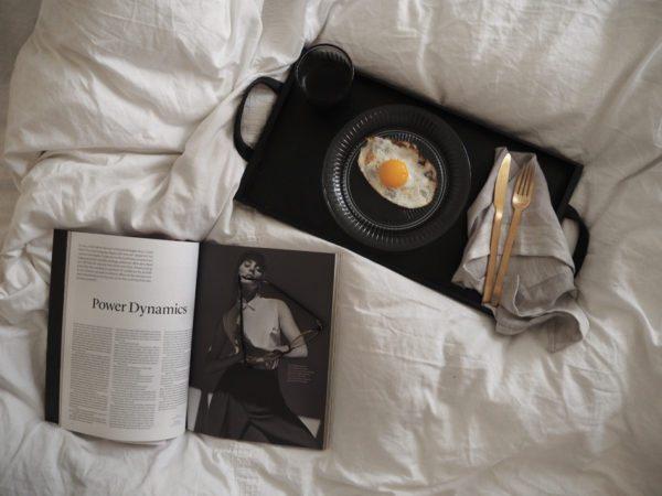 Morgenbakke på sengen. Sort bakke med blå glastallerken med spejlæg, sat i en hvid dyne med et magasin ved siden af og et par briller.