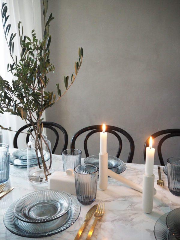 Dækket bord. Smukke blå glas tallerkner fra Kähler placeret på hvidt marmorbord med levende lys og buketter af olivengrene