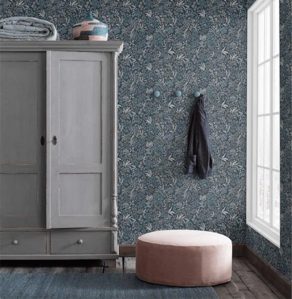Entré med smukt lysegråt gammelt karlekammerskab. Væggene er tapetseret med et smukt og poetisk blå-blomstret tapet og på gulvet står en rund rosa puf