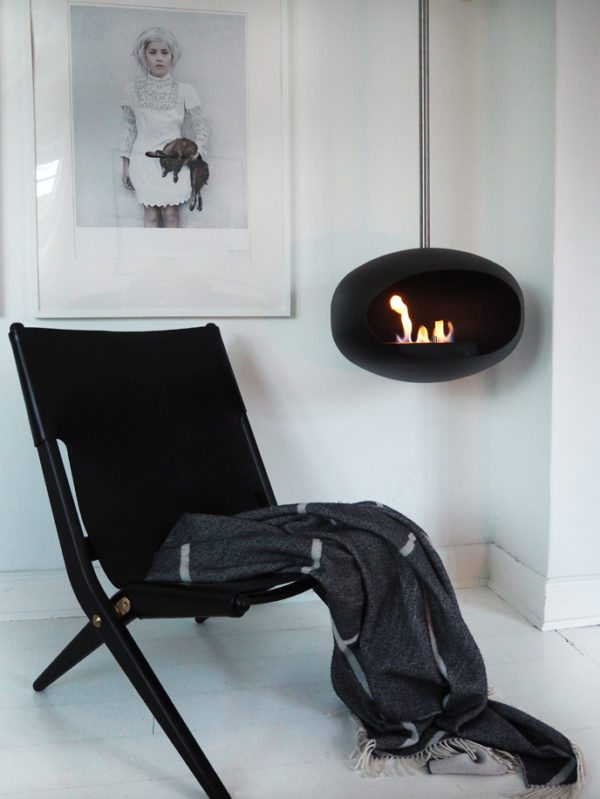 Lounge stol af Mogens Lassen designet i 1955. Her er den placeret foran pejsen med en plaid slynget over sædet