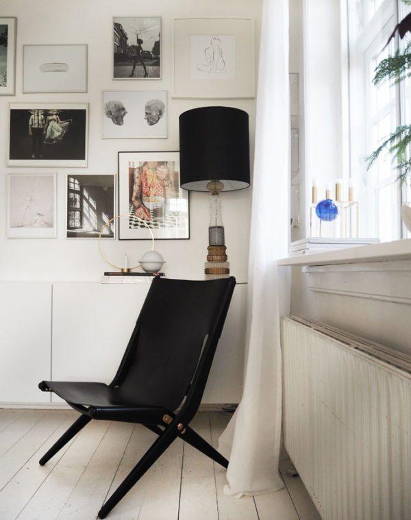 Saxe Lounge chair designet af Mogens Lassen i 1955. Her står den i et hjørne i en stue foran en kunstnerisk billevæg og en skænk med en stor krystallampe